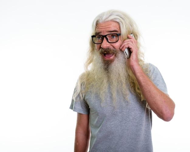 Glücklicher älterer bärtiger mann, der lächelt und denkt, während er am telefon spricht