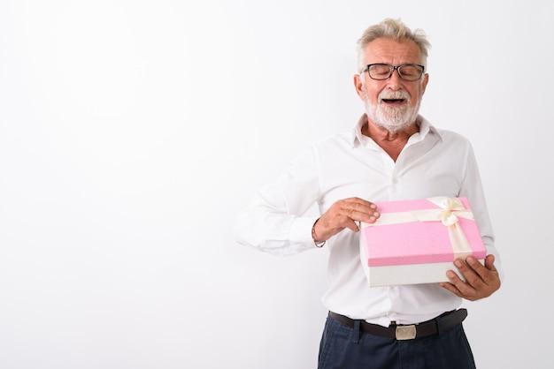 Glücklicher älterer bärtiger mann, der lächelt, während er die augen der geschenkbox öffnet, die auf weiß geschlossen werden