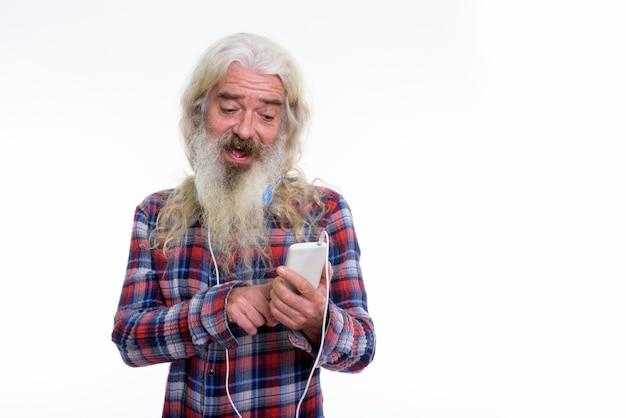 Glücklicher älterer bärtiger mann, der lächelt, während er kopfhörer trägt