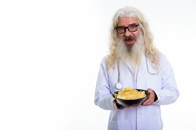 Glücklicher älterer bärtiger mannarzt, der lächelt, während er schüssel kartoffel hält
