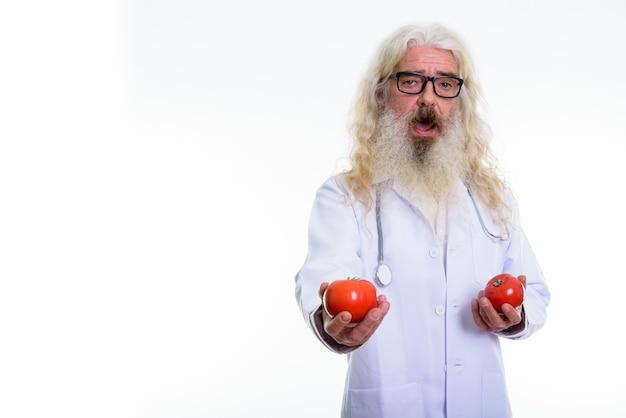 Glücklicher älterer bärtiger mannarzt, der lächelt, während er zwei tomaten hält
