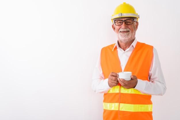 Glücklicher älterer bärtiger mannbauarbeiter, der lächelt und kaffeetasse hält, während brillen auf weiß tragen