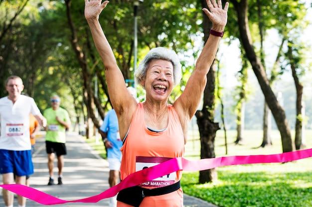 Glücklicher älterer, der durch die ziellinie läuft