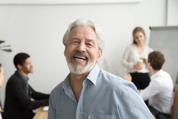 Glücklicher älterer geschäftsmann, der kamera im büro, porträt betrachtend lacht