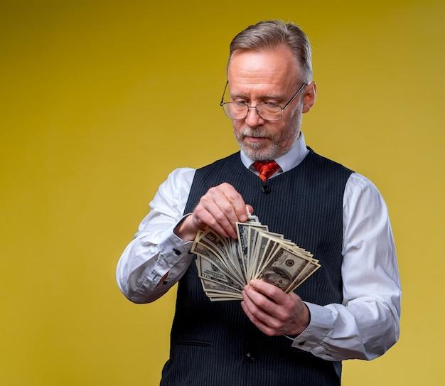 Glücklicher älterer geschäftsmann mit fan von dollarnoten lokalisiert auf gelbem hintergrund. älterer mann hat die lotterie gewonnen. glückstag. menschliche emotionen und mimik