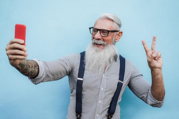 Glücklicher älterer hipster-mann, der selfie mit handy draußen in der stadt tut - fokus auf gesicht