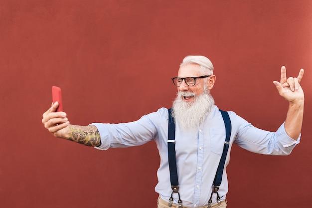 Glücklicher älterer influencer, der online auf handy im freien in der stadt strömt