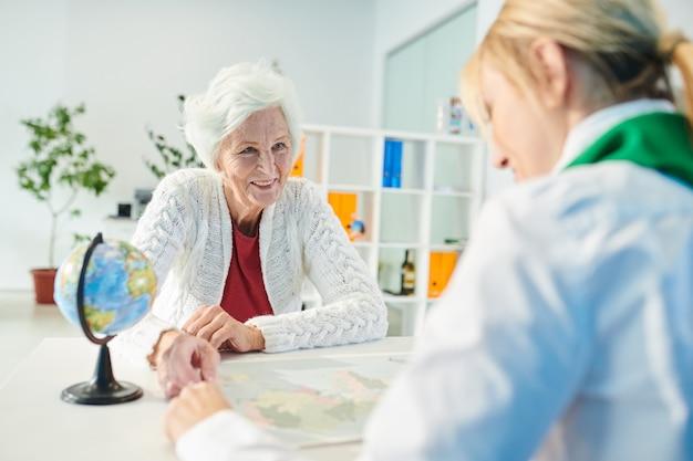 Glücklicher älterer kunde, der reiserichtung mit manager wählt