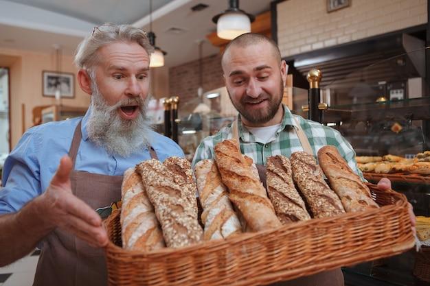 Glücklicher älterer männlicher bäcker, der genießt, mit seinem sohn in seinem brotladen zu arbeiten