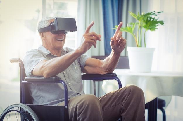 Glücklicher älterer mann auf rollstuhl unter verwendung vr-kopfhörers