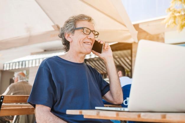 Glücklicher älterer mann, der am handy mit laptop caf� im freien spricht
