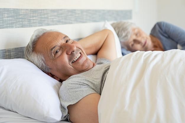 Glücklicher älterer mann, der auf bett liegt