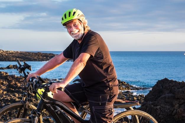 Glücklicher älterer mann, der auf der klippe steht, die seinen bici reitet und kamera betrachtet. zwei elektrofahrräder in der nähe von ihm. blaues meerwasser im hintergrund. abendlicht