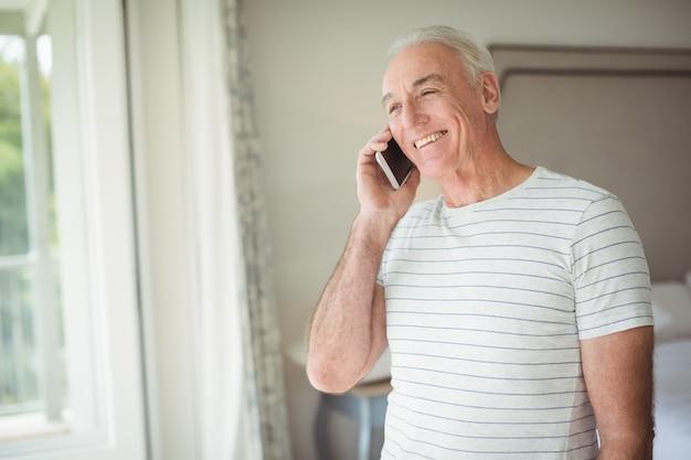Glücklicher älterer mann, der auf handy spricht