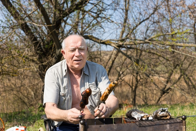 Glücklicher älterer mann, der auf seinem rollstuhl sitzt fertiges grillfleisch auf stöcken im park an einem sehr sonnigen tag sitzt.
