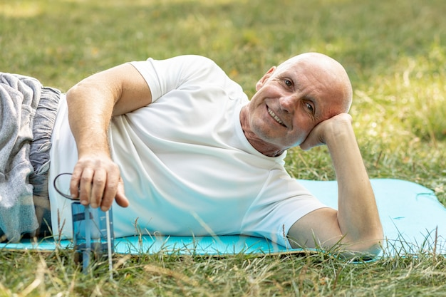 Glücklicher älterer mann, der auf yogamatte auf gras stillsteht