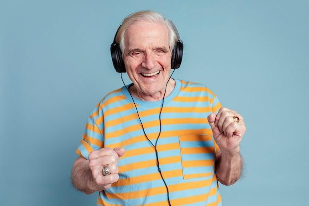 Glücklicher älterer mann, der beim musikhören mit kopfhörern tanzt