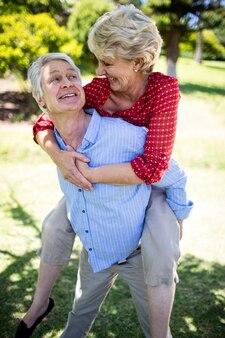 Glücklicher älterer mann, der der älteren frau ein doppelpol gibt