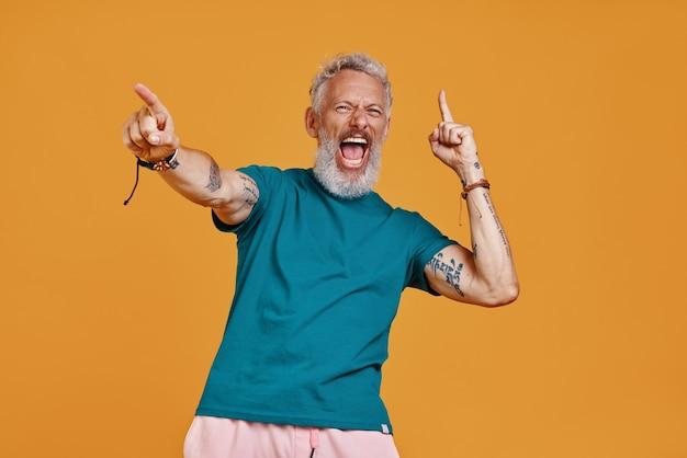 Glücklicher älterer mann, der die arme ausgestreckt hält und schreit