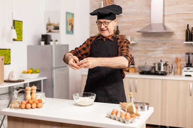 Glücklicher älterer mann, der eier über weizenmehl knackt, während er traditionelles rezept zubereitet. älterer konditor, der eier auf glasschüssel für kuchenrezept in der küche knackt, von hand mischen, kneten