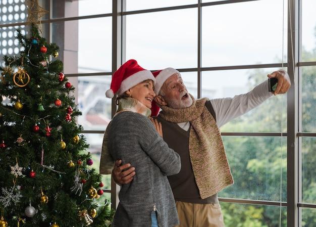 Glücklicher älterer mann, der ein paar umarmt und zusammen mit dem handy selfie macht und im winter neben dem dekorierten weihnachtsbaum im gemütlichen wohnzimmer mit außenansichtsfenster steht. frohe weihnachten.