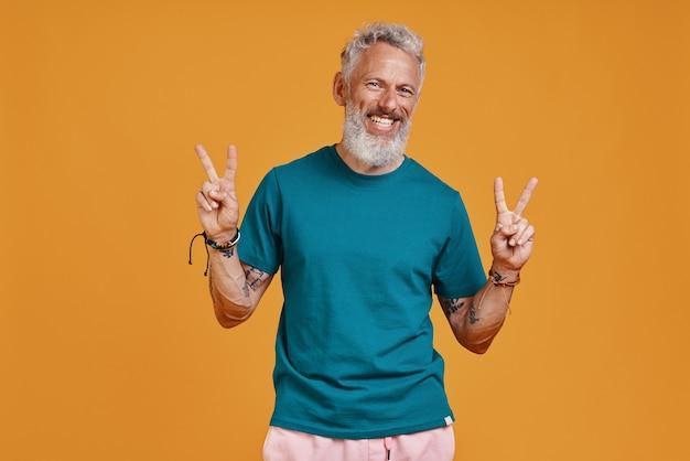 Glücklicher älterer mann, der gestikuliert und lächelt