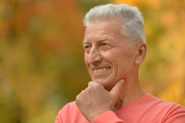 Glücklicher älterer mann, der im herbstpark genießt