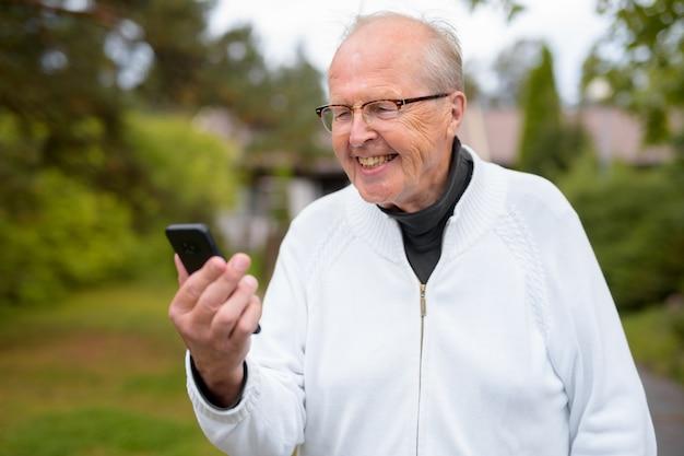 Glücklicher älterer mann, der lächelt, während er telefon zu hause im freien benutzt