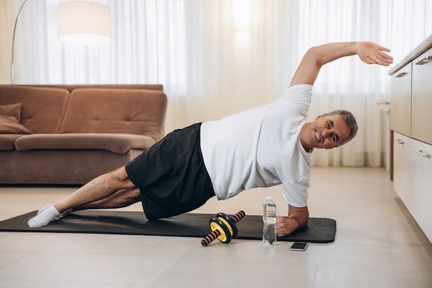 Glücklicher älterer mann, der mit erhobener hand seitliche plankenübungen macht, lächelt und nach vorne schaut