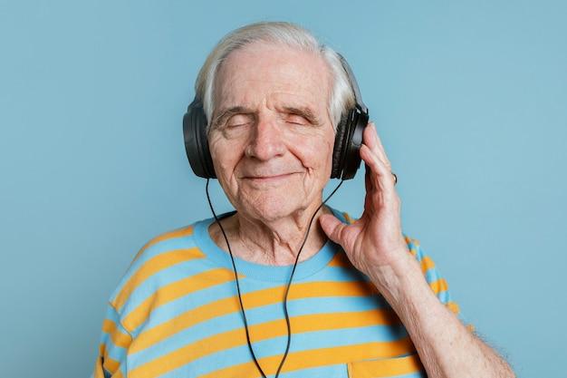 Glücklicher älterer mann, der musik mit kopfhörern hört