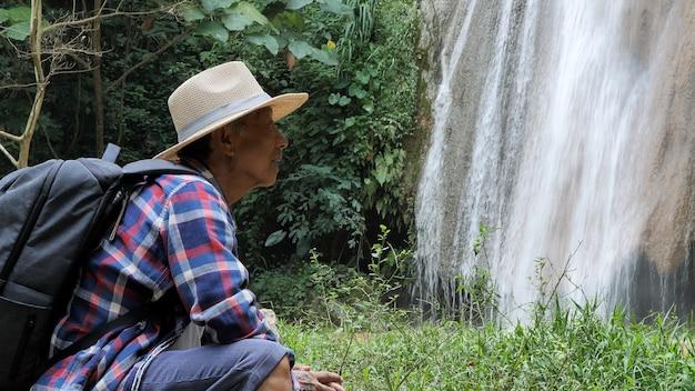 Glücklicher älterer mann, der nahe dem wasserfall genießt erstaunliche ansicht sitzt