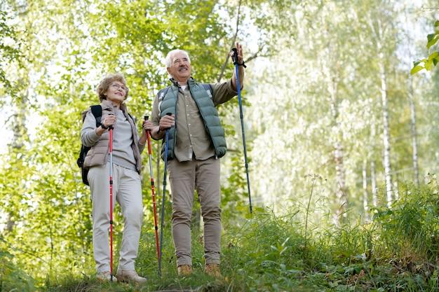 Glücklicher älterer mann, der seiner frau den weg zum wald zeigt, während er in der natürlichen umgebung steht