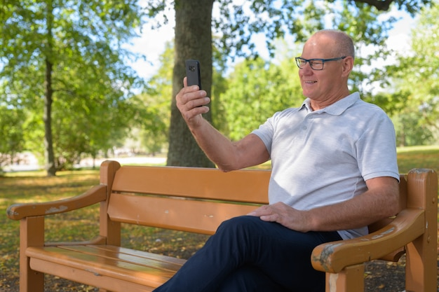 Glücklicher älterer mann, der sitzt und selfie im park nimmt
