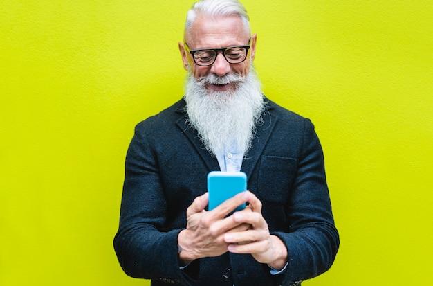 Glücklicher älterer mann, der smartphone-app mit fluoreszierender farbe verwendet. hipster alter mann, der spaß mit technologie hat