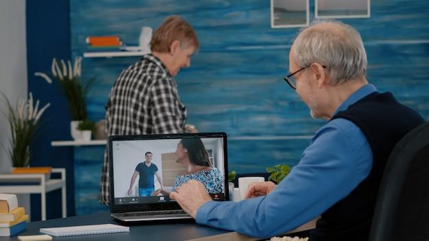 Glücklicher älterer mann, der während der videokonferenz mit neffen mit laptop im wohnzimmer winkt. ältere person, die die video-webcam der internet-online-chat-technologie verwendet, um einen virtuellen meeting-videoanruf durchzuführen