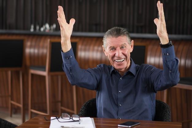 Glücklicher älterer mann heben der arme während in cafe sitzen
