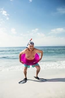 Glücklicher älterer mann im aufblasbaren ring und in den flossen, die am strand stehen