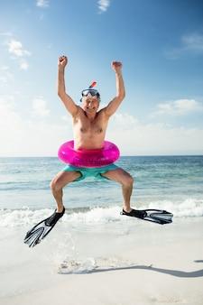 Glücklicher älterer mann im aufblasbaren ring und in den flossen, die auf strand springen