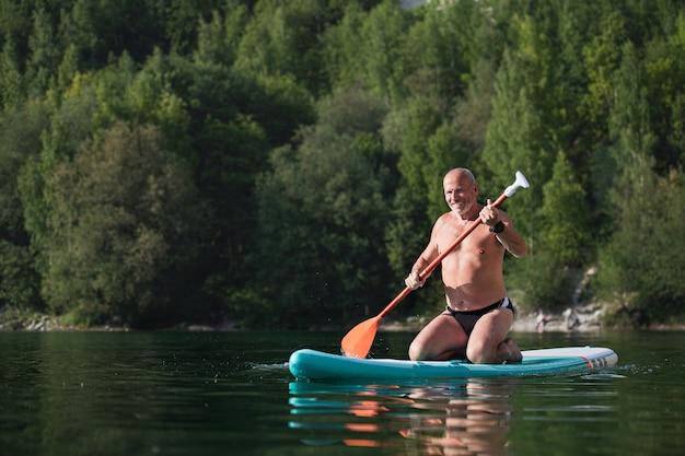 Glücklicher älterer mann im sommerurlaub am see, paddleboarding.