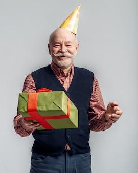 Glücklicher älterer mann in der parteimütze hält geschenkbox. fröhlicher reifer senior