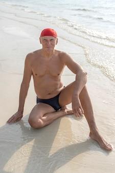 Glücklicher älterer mann in einem roten badehut am strand in der nähe des meerwassers