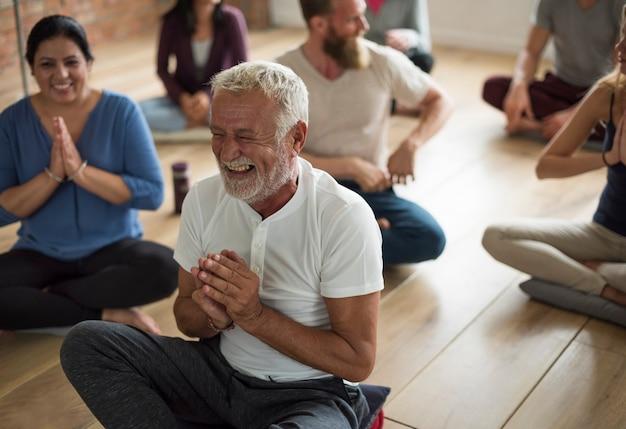 Glücklicher älterer mann in einem yogakurs