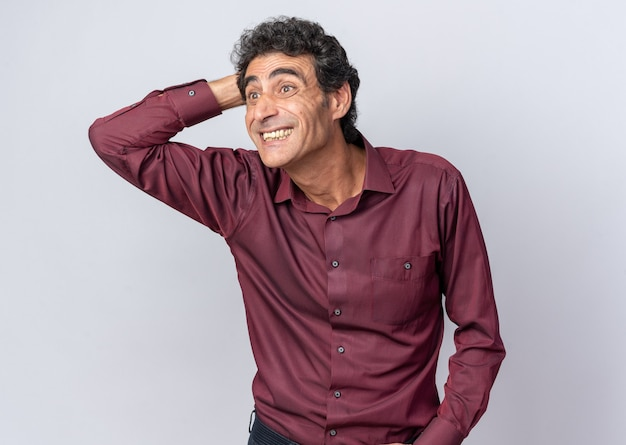 Glücklicher älterer mann in lila hemd, der erstaunt und überrascht mit der hand auf dem kopf auf weißem hintergrund beiseite schaut