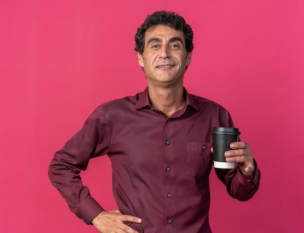 Glücklicher älterer mann in lila hemd mit pappbecher, der selbstbewusst in die kamera schaut