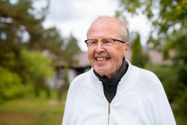 Glücklicher älterer mann mit brille, die zu hause lächelt und denkt ou