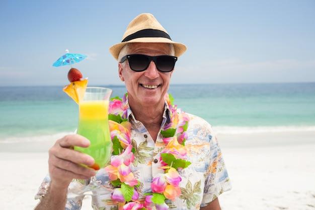 Glücklicher älterer mann mit einem cocktailgetränk