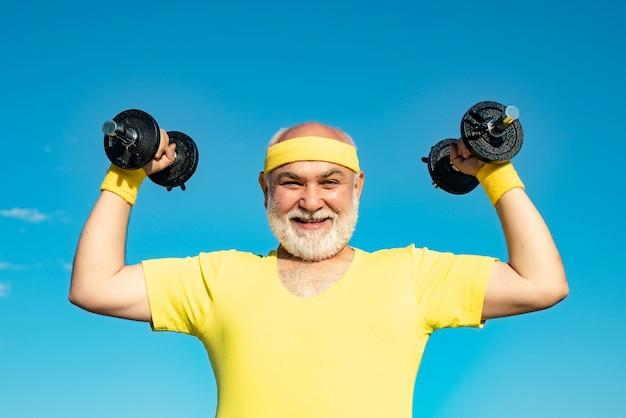 Glücklicher älterer mann mit hantel mit blick auf die körperpflege der kamera und den großvater-sportler-port im gesundheitswesen...