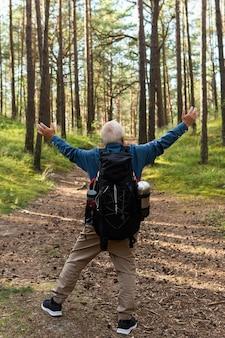 Glücklicher älterer mann mit offenen armen rucksack in der natur