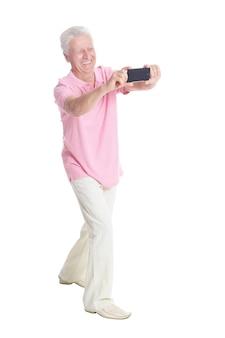 Glücklicher älterer mann mit smartphone, der selfie auf weißem hintergrund macht