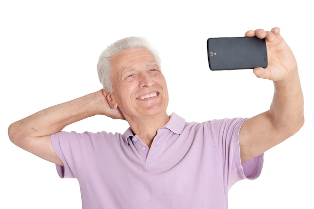 Glücklicher älterer mann mit smartphone, der selfie-foto auf weißem hintergrund macht